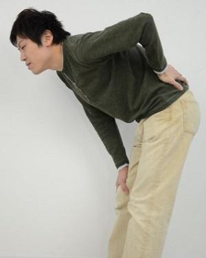 腰痛で腰を押さえる男性