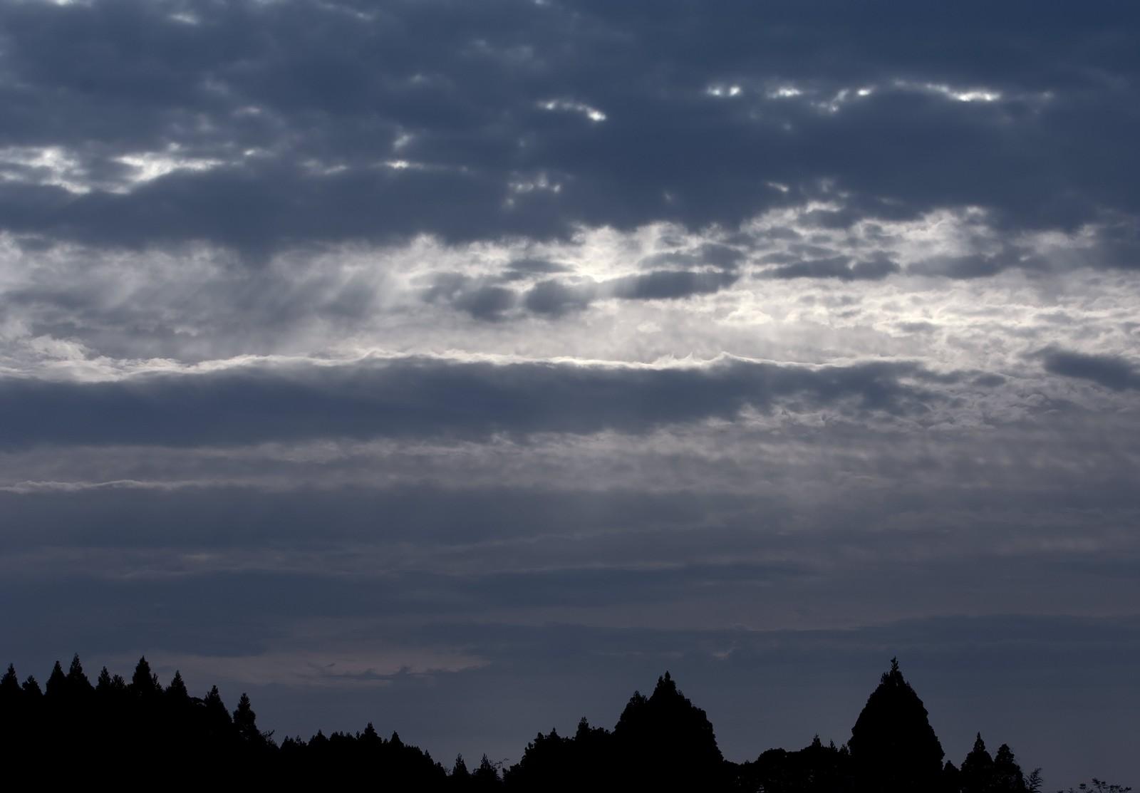 曇り空の雲間から光がさす
