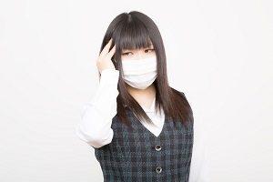 風邪をひいたのかマスクをする女性